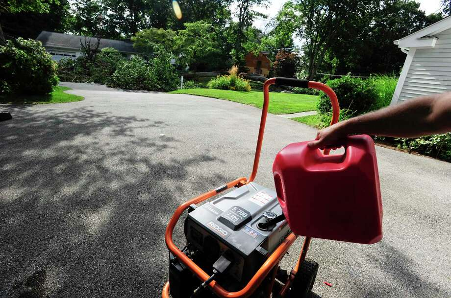 A neighbor fills their generator with gas on August 8, 2020 in Stamford, Connecticut, as they wait for Eversource and the City of Stamford to clear a fallen tree blocking access to Bertmor Lane and restore power to the neighborhood. Photo: Matthew Brown / Hearst Connecticut Media / Stamford Advocate