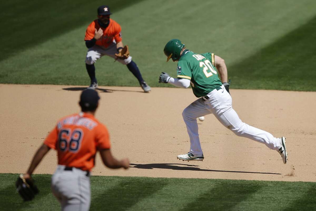 Oakland Athletics center fielder Mark Canha (20) runs to first and is forced out in a double play during an MLB game against the Houston Astros at RingCentral Coliseum on Saturday, Aug. 8, 2020, in Oakland, Calif.