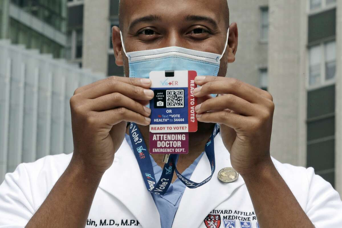 Alister Martin, an emergency room doctor at Massachusetts General Hospital in Boston, holds up a voter information card he wears on his ID lanyard, which gives patients a Q-code and text link to help them register to vote.