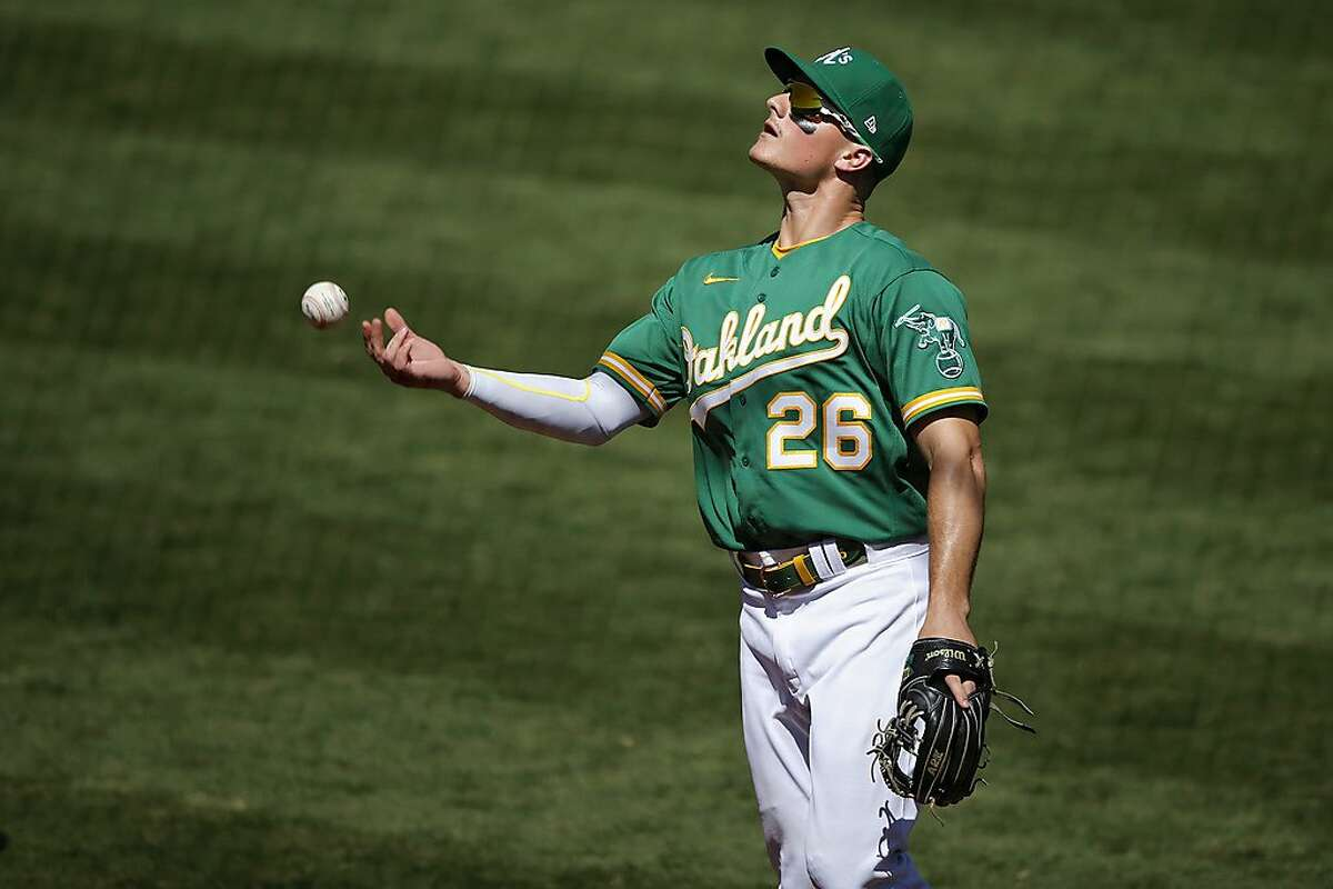Oakland Athletics third baseman Matt Chapman (26) throws the ball into the stands as he heads to the dugout during an MLB game against the Houston Astros at RingCentral Coliseum on Saturday, Aug. 8, 2020, in Oakland, Calif. The A's won 3-1.