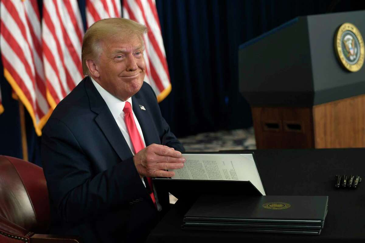 President Donald Trump smiles as he is about to sign four executive orders during a news conference at the Trump National Golf Club in Bedminster, N.J., Saturday, Aug. 8, 2020. (AP Photo/Susan Walsh)