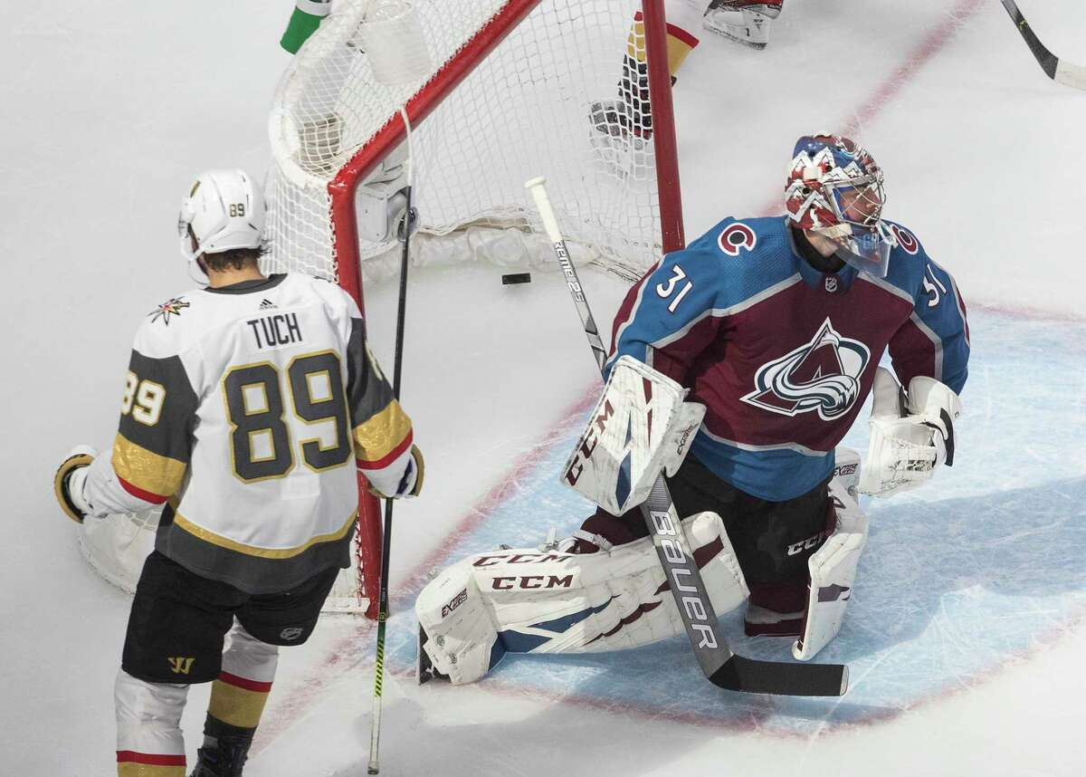 Colorado Avalanche goalie Philipp Grubauer (31) gives up a goal to Vegas Golden Knights' Alex Tuch (89) during the third period of an NHL hockey playoff game in Edmonton, Alberta, Saturday, Aug. 8, 2020. (Jason Franson/The Canadian Press via AP)