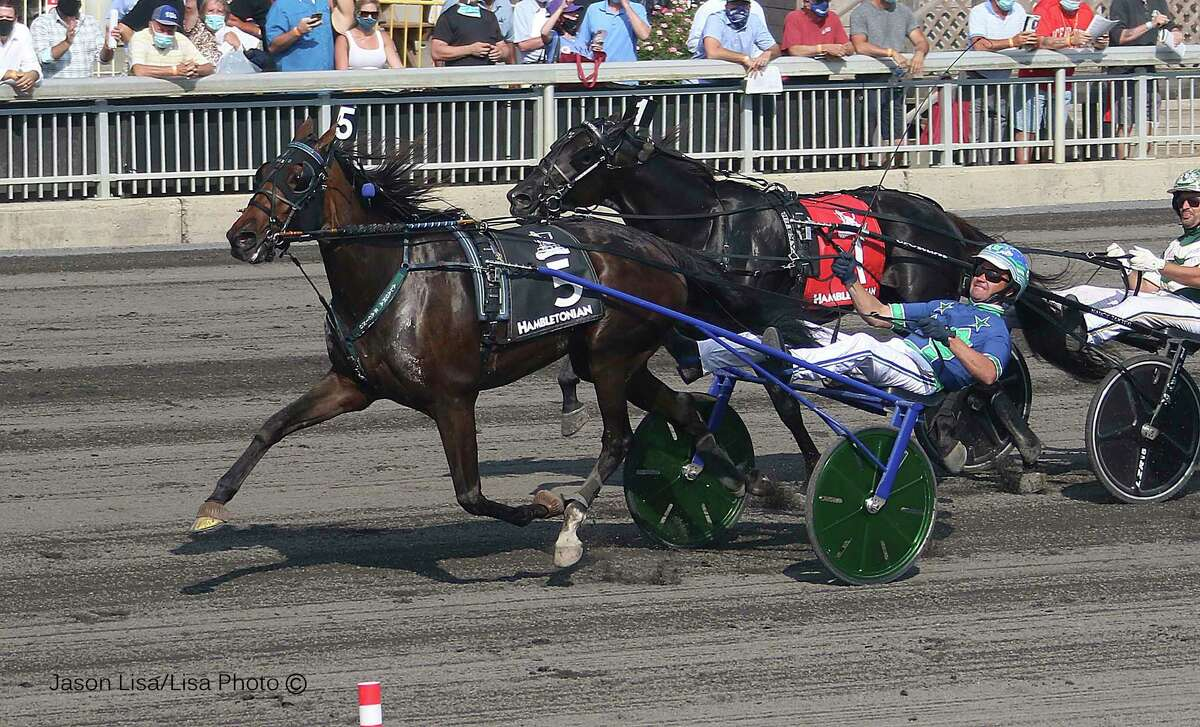 In a photo provided by Lisa Photo, Ramona Hill, driven by Andrew McCarthy, wins the 95th Hambletonian horse race at the Meadlowlands in East Rutherford, N.J., Saturday, Aug. 8, 2020. (Jason Lisa/Lisa Photos via AP)