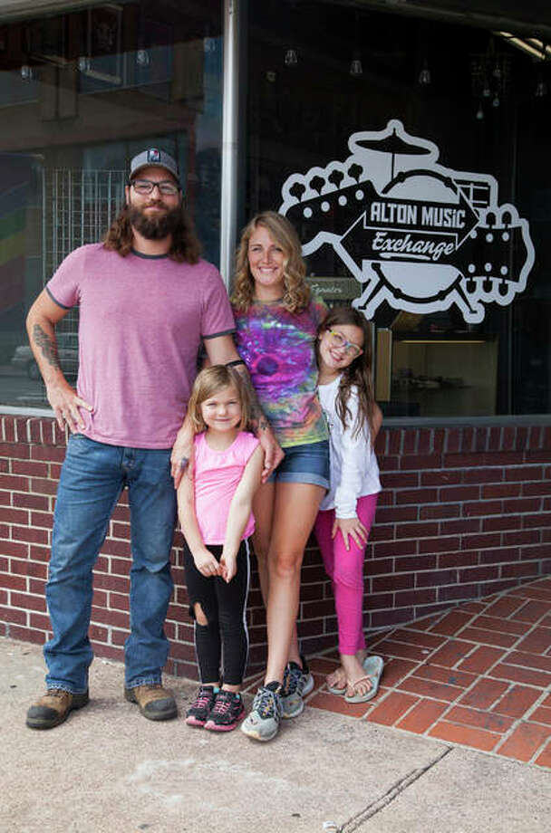 Jared and Jenny Unfried with their two daughters in front of their newly opened music store, Alton Music Exchange, 556 E. Broadway in Downtown Alton. By encouraging local musicians to bring in guitars, amps and whatever else they might have for trade or sale, the couple hopes to build a hub for local musicians and strengthen the local music community. Photo: Jeanie Stephens |The Telegraph