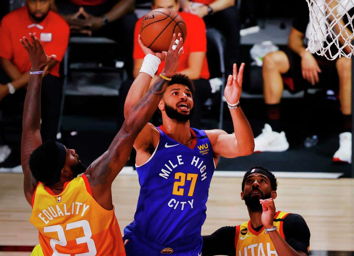 Denver Nuggets' Jamal Murray (27) drives the ball against Utah Jazz's Royce O'Neale and Mike Conley, right, during the second quarter of an NBA basketball game Saturday, Aug. 8, 2020, in Lake Buena Vista, Fla. (Kevin C. Cox/Pool Photo via AP)