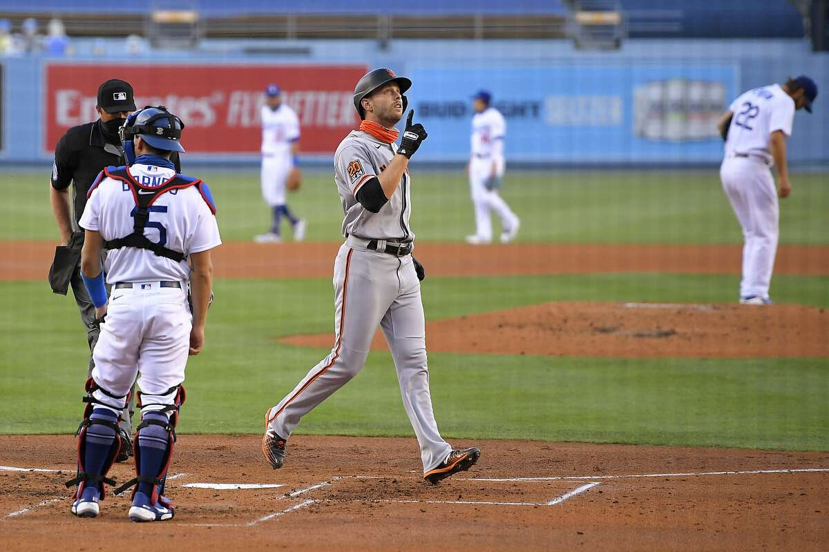 San Francisco Giants' Austin Slater, front right, gestures as he scores after hitting a solo home run, while Los Angeles Dodgers catcher Austin Barnes, left, and starting pitcher Clayton Kershaw, back right, stand at their positions during the third inning of a baseball game Saturday, Aug. 8, 2020, in Los Angeles. (AP Photo/Mark J. Terrill)
