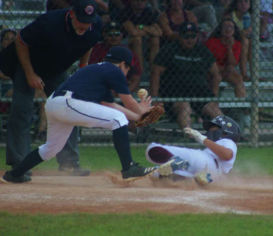 League City American 11s all-star Andrew Maston slides home with a run despite the best efforts of NASA all-star Jacob McBride, who can't find the handle on the catcher's toss. Photo: Robert Avery