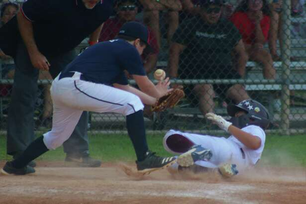 League City American 11s all-star Andrew Maston slides home with a run despite the best efforts of NASA all-star Jacob McBride, who can't find the handle on the catcher's toss.