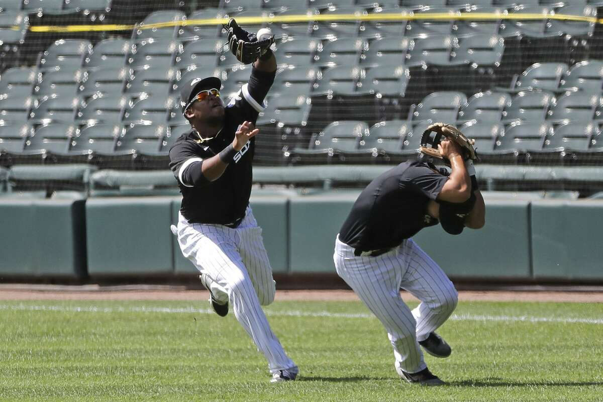 Chicago White Sox right fielder Luis Alexander Basabe, left, catches a ball hit by Luis Robert as second baseman Nick Madrigal covers his head during an intra-squad baseball game at Guaranteed Rate Field in Chicago, Tuesday, July 14, 2020. (AP Photo/Nam Y. Huh)