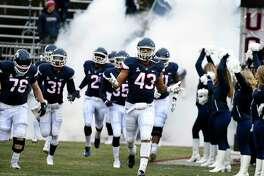 UConn players take the field before a game against Temple at Rentschler Field.