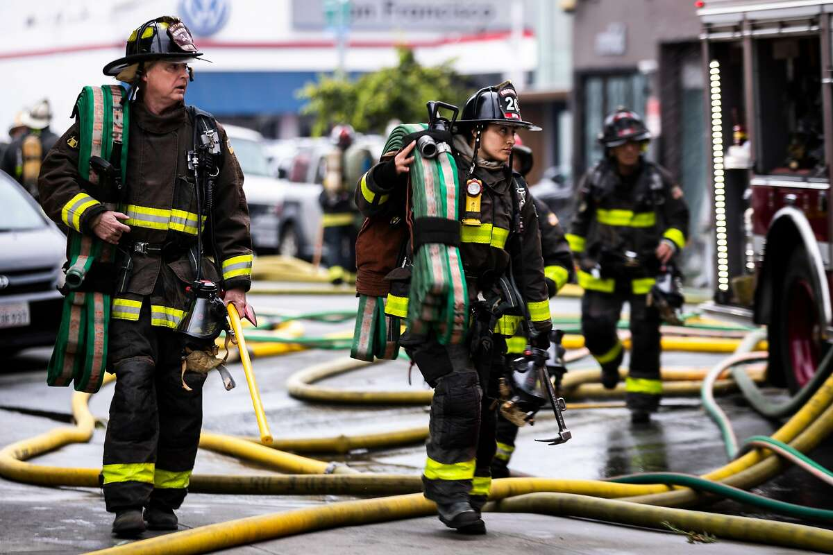 Firefighters carry equipment at the scene of a five-alarm structure fire in the South of Market neighborhood in San Francisco, Calif. on Tuesday, July 28, 2020.