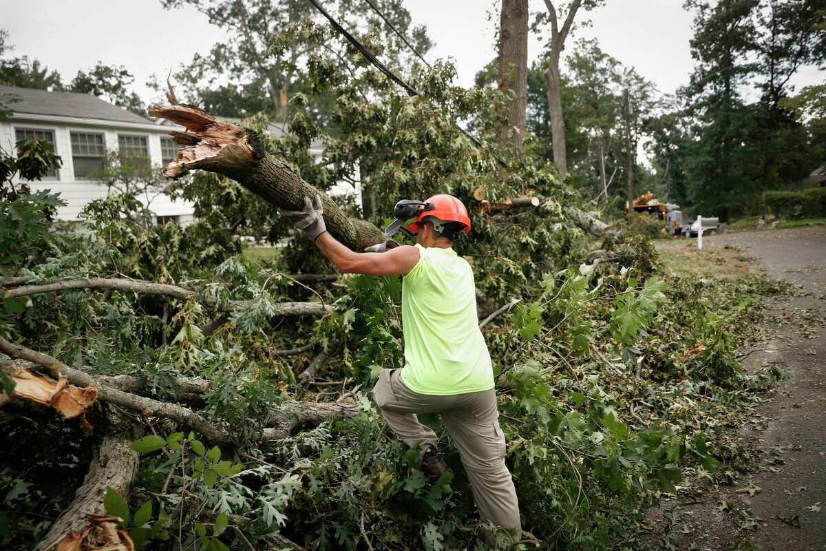 Work crews clear storm debris amid deactivated power lines, Friday, Aug. 7, 2020, in Westport, Conn. The Connecticut National Guard joined over 1,750 utility crews in Connecticut in efforts to clear trees and restore power to more than 400,000 homes and businesses still in the dark, as frustration continued to grow over the pace of the response to Tropical Storm Isaias. (AP Photo/John Minchillo)