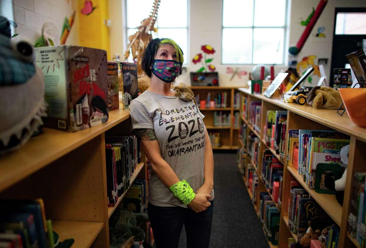 Link, a calm bearded dragon, sits on the shoulder of Forester Elementary School librarian Kat Lowe as she walks around the library, A self-described punk rocker, Lowe encourages students to live life loudly and proudly.