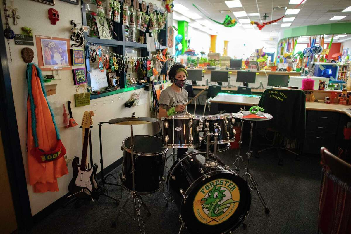 """Forester Elementary School librarian Kat Lowe plays drums in her library on Monday, Aug. 3, 2020. She encourages students to live life loudly as evidenced by the drums. She often answers with her drumsticks when kids ask her, """"Ms. Lowe, can you drop a beat?"""""""