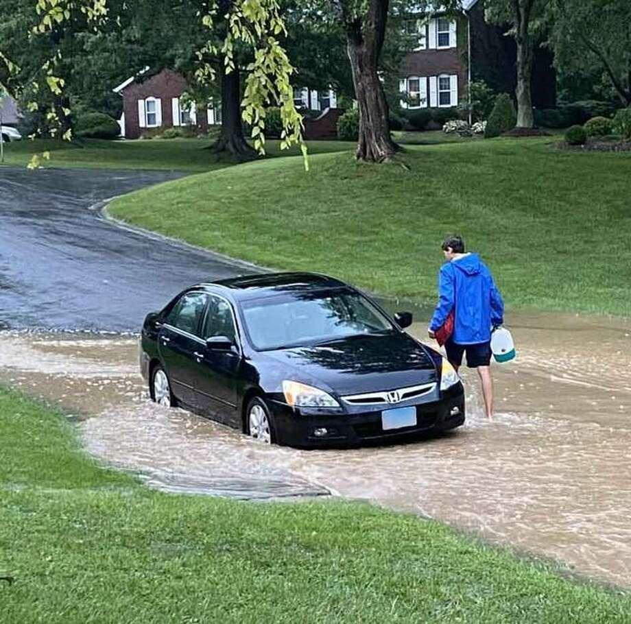 Rising flood waters force a motorist to move a car Sunday morning near Waterford Lane in Glen Carbon. Illinois State Police assisted Glen Carbon's fire and police departments in response to calls of multiple vehicles and passengers stranded on Route 162 Sunday morning due to flash flooding. Photo: Submitted Photo|For The Telegraph