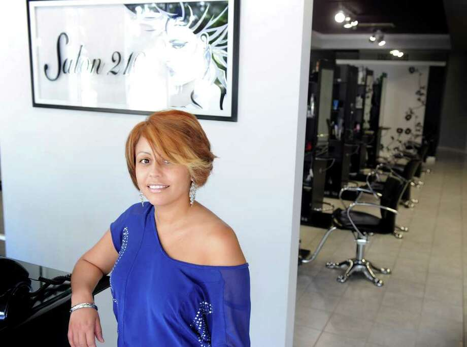 Stylist and co-owner Jessica Portillo stands in the lobby of Salon 210 in Stratford.  After seven years in Bridgeport, the business moved to a larger space and is soon to open a cosmetology school. Photo: Autumn Driscoll / Connecticut Post