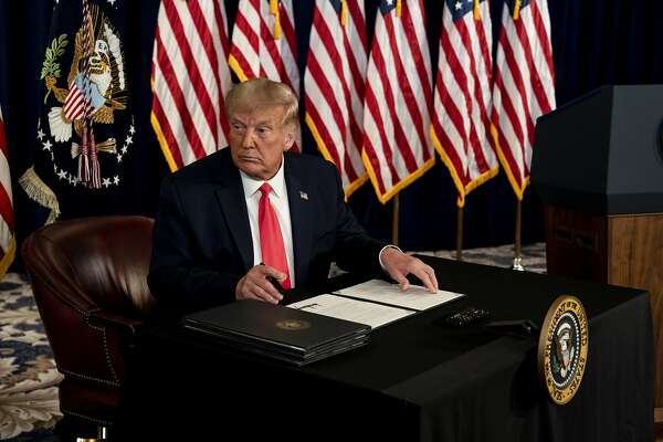 President Donald Trump signs an executive order related to coronavirus pandemic relief during a news conference at Trump National Golf Club in Bedminster, N.J., on Aug. 8, 2020. (Anna Moneymaker/The New York Times)