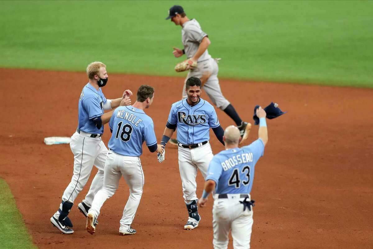 ST. PETERSBURG, FL - AUGUST 9: Austin Meadows #17 of the Tampa Bay Rays, left, joins Joey Wendle #18 and Michael Brosseau #43 in congratulating Michael Perez #7 after his game-winning hit in front of DJ LeMahieu #26 of the New York Yankees during the ninth inning of a baseball game at Tropicana Field on August 9, 2020 in St. Petersburg, Florida. (Photo by Mike Carlson/Getty Images)