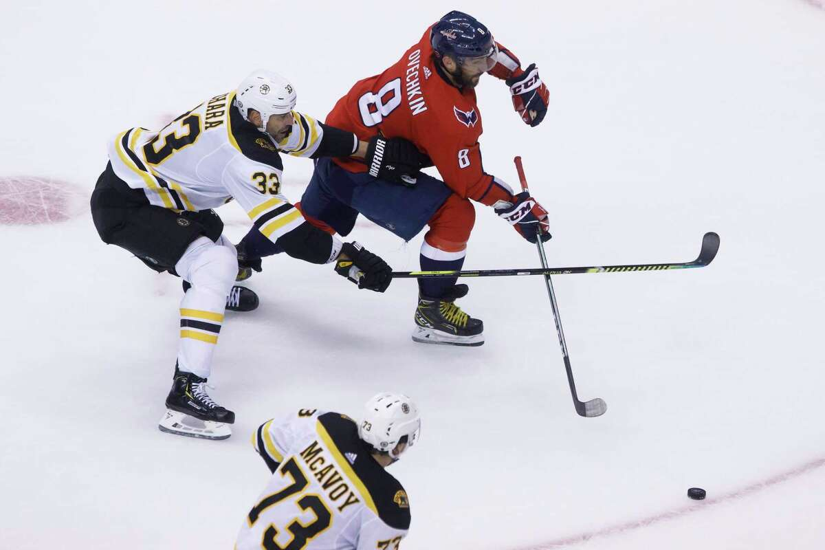 Washington Capitals left wing Alex Ovechkin (8) maneuvers the puck around Boston Bruins defenseman Zdeno Chara (33) during second-period NHL Stanley Cup qualifying round game action in Toronto, Sunday, Aug. 9, 2020. (Cole Burston/The Canadian Press via AP)