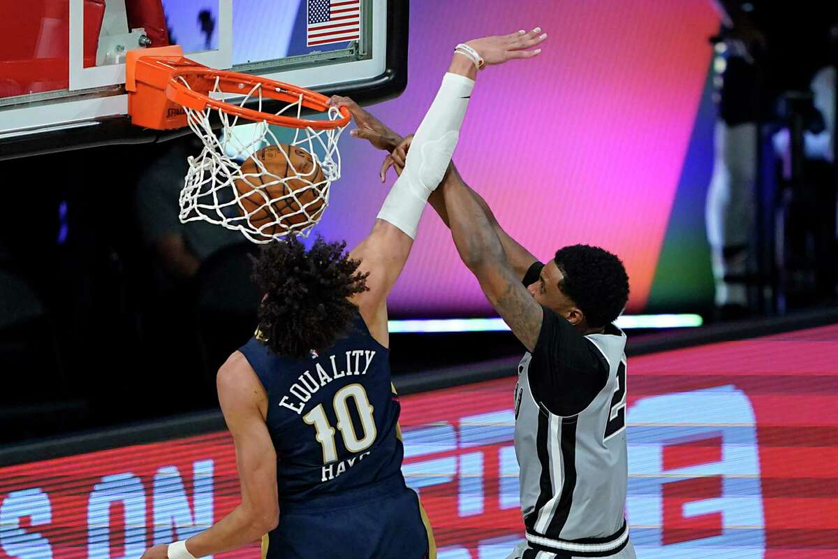 San Antonio Spurs' Rudy Gay, right, dunks the ball as he gets past New Orleans Pelicans' Jaxson Hayes (10) during the second half of an NBA basketball game, Sunday, Aug. 9, 2020, in Lake Buena Vista, Fla. (AP Photo/Ashley Landis, Pool)