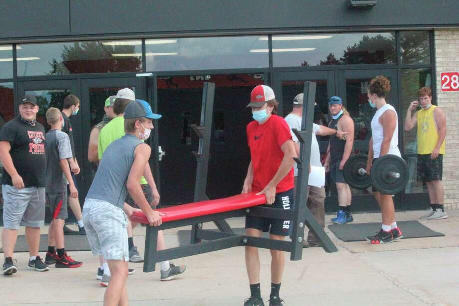 Reed City football players get weight-lifting equipment set up outside on Thursday night. (Pioneer photo/John Raffel)
