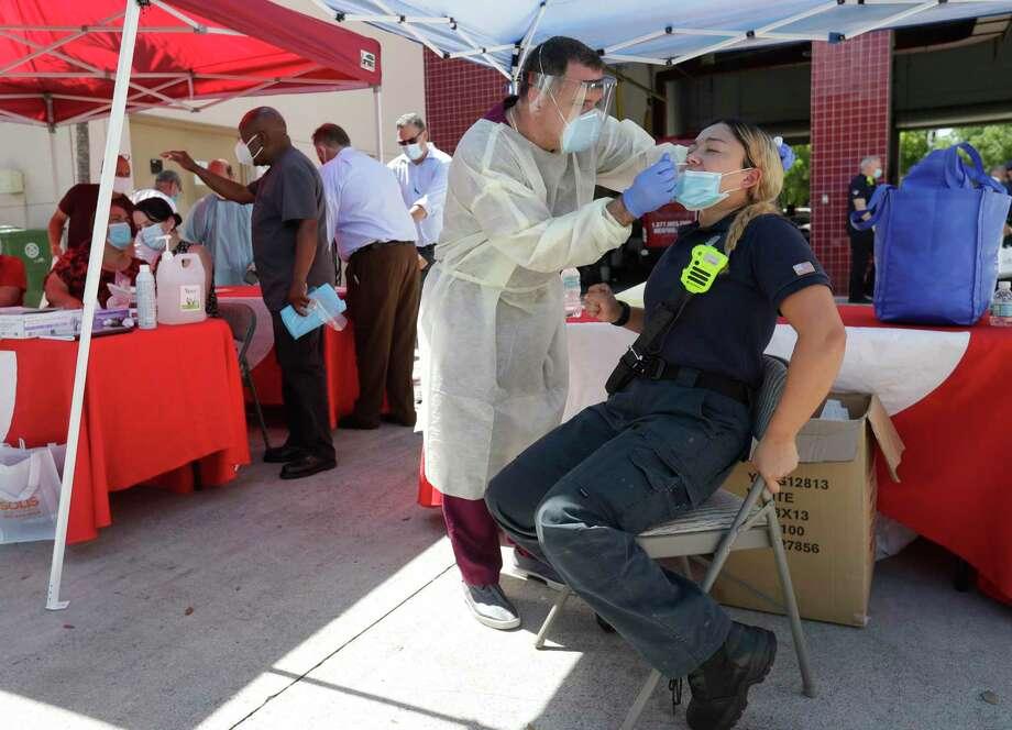 El asistente médico Jesús Vera realiza una prueba de coronavirus a la paramédica Laura Nemoga, en Hialeah, Florida, el 6 de agosto de 2020. Photo: Wilfredo Lee /Associated Press / Copyright 2020 The Associated Press. All rights reserved
