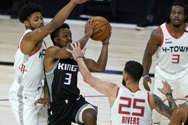 Yogi Ferrell #3 of the Sacramento Kings drives to the basket against Austin Rivers #25 and Bruno Caboclo #5 of the Houston Rockets during the second half at HP Field House at ESPN Wide World Of Sports Complex on August 9, 2020 in Lake Buena Vista, Florida. (Photo by Ashley Landis-Pool/Getty Images)
