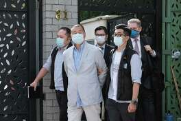 Jimmy Lai, chairman of Next Digital Ltd., second left, is led away from his residence by law enforcement officials in Hong Kong on Aug. 10, 2020.