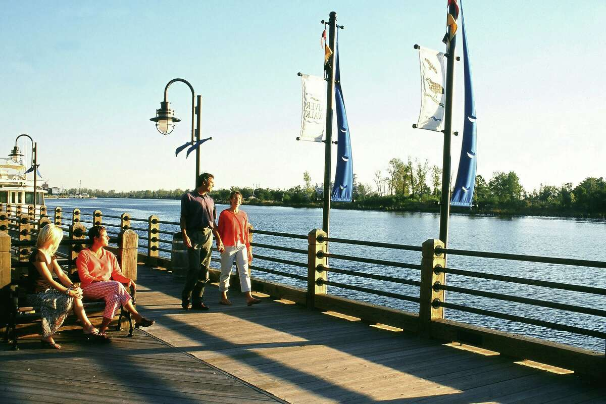 People stroll along the riverfront in Wilmington, with views of the Cape Fear River.
