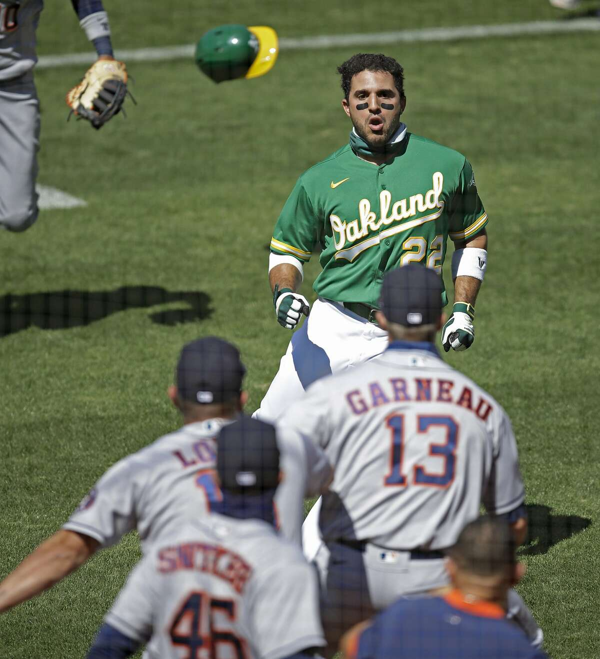 Oakland Athletics' Ramon Laureano (22) charges the Houston Astros' dugout after being hit by a pitch thrown by Humberto Castellanos during the seventh inning of a baseball game Sunday, Aug. 9, 2020, in Oakland, Calif.