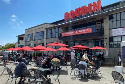 People enjoy lunch in a crowded outdoor area of a Pier 45 restaurant in San Francisco, California on August 2, 2020 amid the coronavirus pandemic.