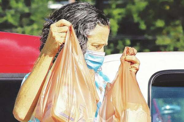 A woman unloading her groceries from the Godfrey Schnucks store recently wears a face mask, like all of the store's customers and employees, to slow the spread of the COVID-19 virus. On Monday, the Madison County Health Department announced 19 opportunities for COVID-19 community testing sites.