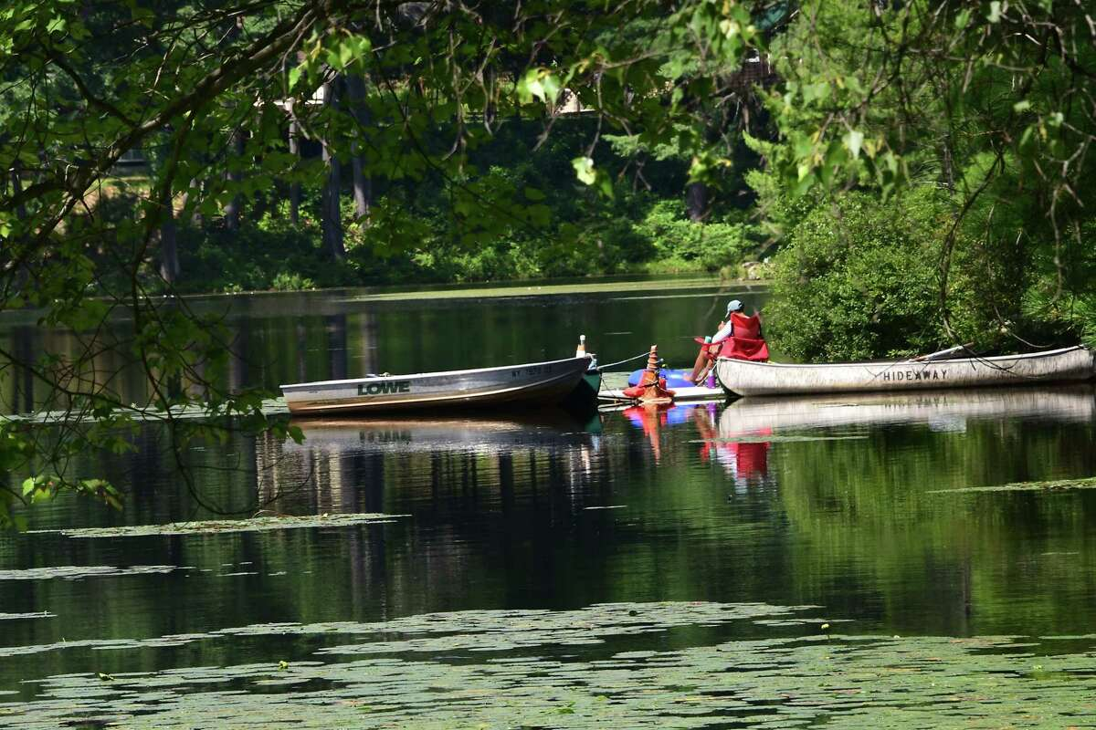 A person is seen sitting along the tranquil Lake Vanare on Monday, Aug. 10, 2020 in Lake Luzerne, N.Y. (Lori Van Buren/Times Union)