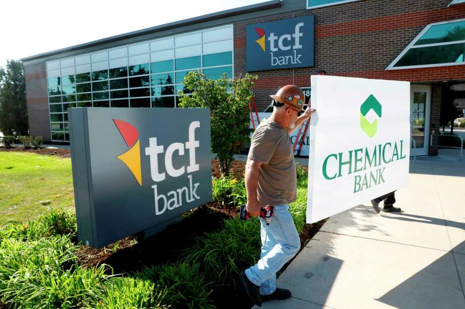 Universal Sign employees Kris Suhr (in brown shirt) and Eddie Bruining change over the Chemical Bank signs at the bank's location on 12 Mile Road in Southfield on Friday, Aug. 7. (Photo provided/TCF)