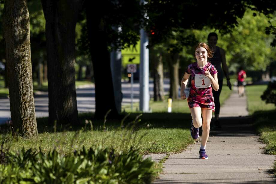 Abigail Granger, 8, completes the running portion of her Tri-Kids-Try triathlon Saturday, Aug. 8, 2020 near her home in Midland. The annual event took on a virtual format this year in light of the coronavirus pandemic, encouraging kids to create and complete their own triathlon at a time and location of their choosing. (Cody Scanlan/for the Daily News) Photo: (Cody Scanlan/for The Daily News)