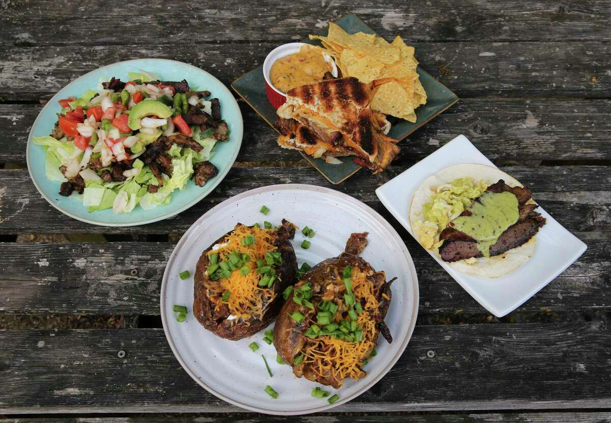 An assortment of food items made with leftover brisket includes (clockwise from left): Brisket Salpicón (Shredded Brisket Salad), Brisket Grilled Cheese, Smoked Brisket Queso, brisket tacos and Brisket Smoked Baked Potatoes.
