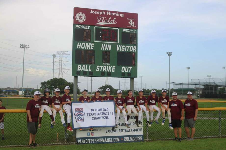 The League City Little League 10-year-old all-stars pose with their newly-captured district championship banner Sunday after their convincing 16-1 triumph. Photo: Robert Avery