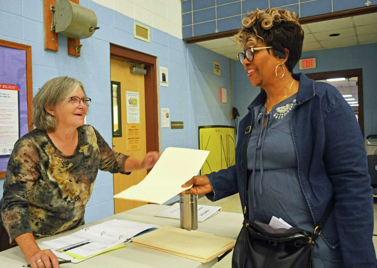 In this archive picture, Middletown resident and election moderator Ann Smith, left, hands a manila folder to a city resident at Macdonough Elementary School during last year's primary vote.