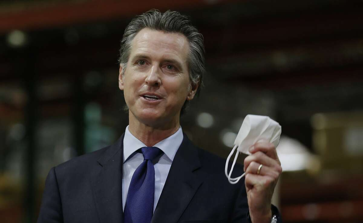 FILE - California Gov. Gavin Newsom displays a face mask as he urges people to wear them to fight the spread of the coronavirus during a news conference in Rancho Cordova, Calif., Friday, June 26, 2020.