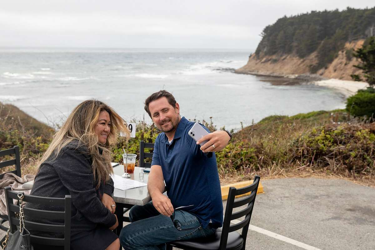 Abigail and Daniel Johnson of San Jose take a selfie after finishing their meal at Moss Beach Distillery in Moss Beach, Calif. Saturday, August 1, 2020. The restaurant has opened their standard patio overlooking the ocean to patrons and have also added extra socially distanced tables in their parking lot.