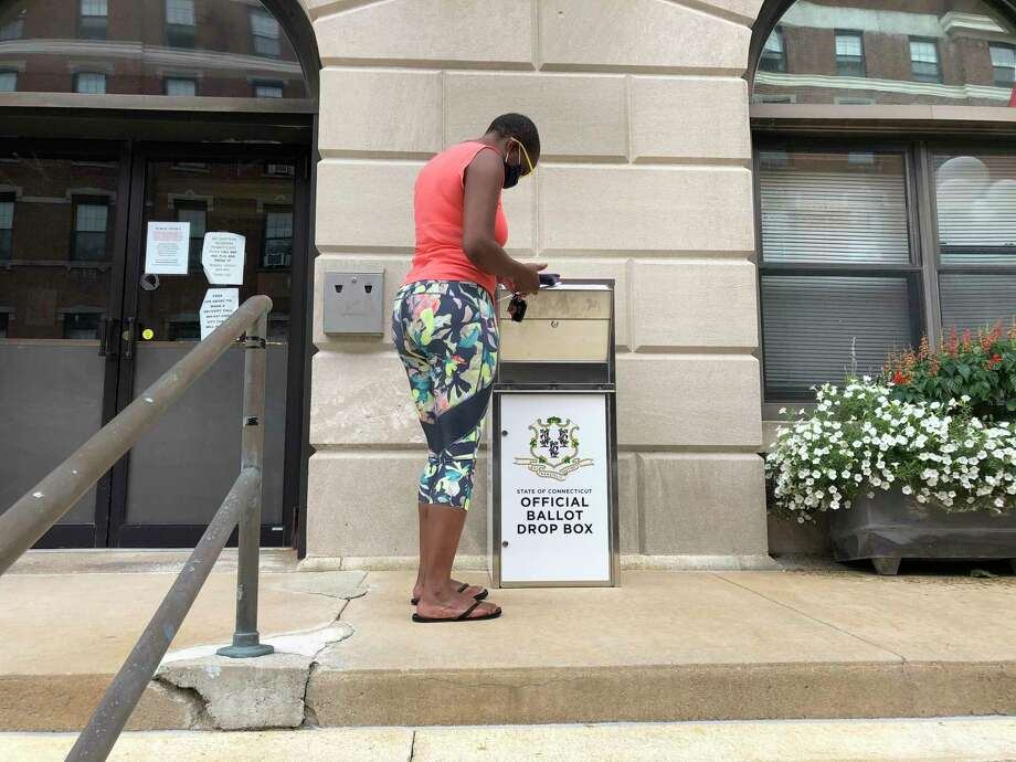 Katrina McKelvin of New London, Conn. on Aug. 6, 2020 deposits her absentee ballot for the Aug. 11 primary in a special box that has been set up outside the New London City Hall. The state of Connecticut used federal coronavirus relief funds to purchase the boxes for each city and town so voters can drop off their ballots instead of having to go personally to the polls. (AP Photo/Susan Haigh) Photo: Susan Haigh / Associated Press / AP