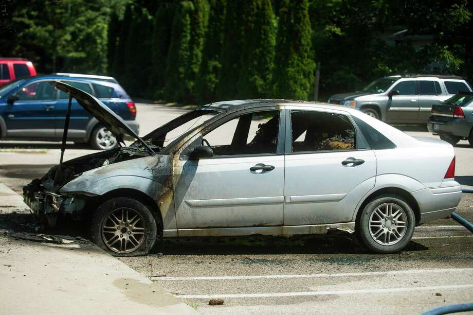 Midland firefighters secure the scene of a car fire after extinguishing the blaze Monday afternoon, Aug. 10, 2020 at an apartment complex off M-20 between Smith and Wildes. (Katy Kildee/kkildee@mdn.net)