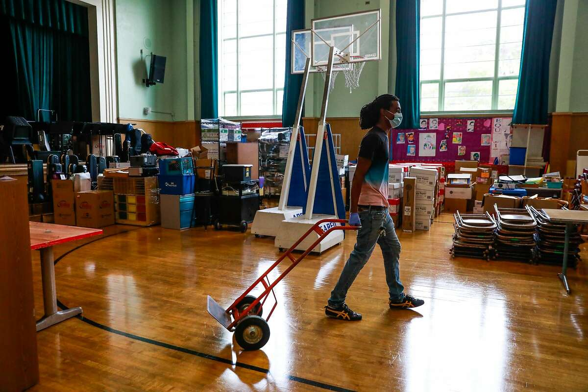 Head custodian Ashanti Lewis pulls a dolly as he works on organizing the assembly room at Sankofa Academy on the first day of school on Monday, Aug. 10, 2020 in Oakland, California.