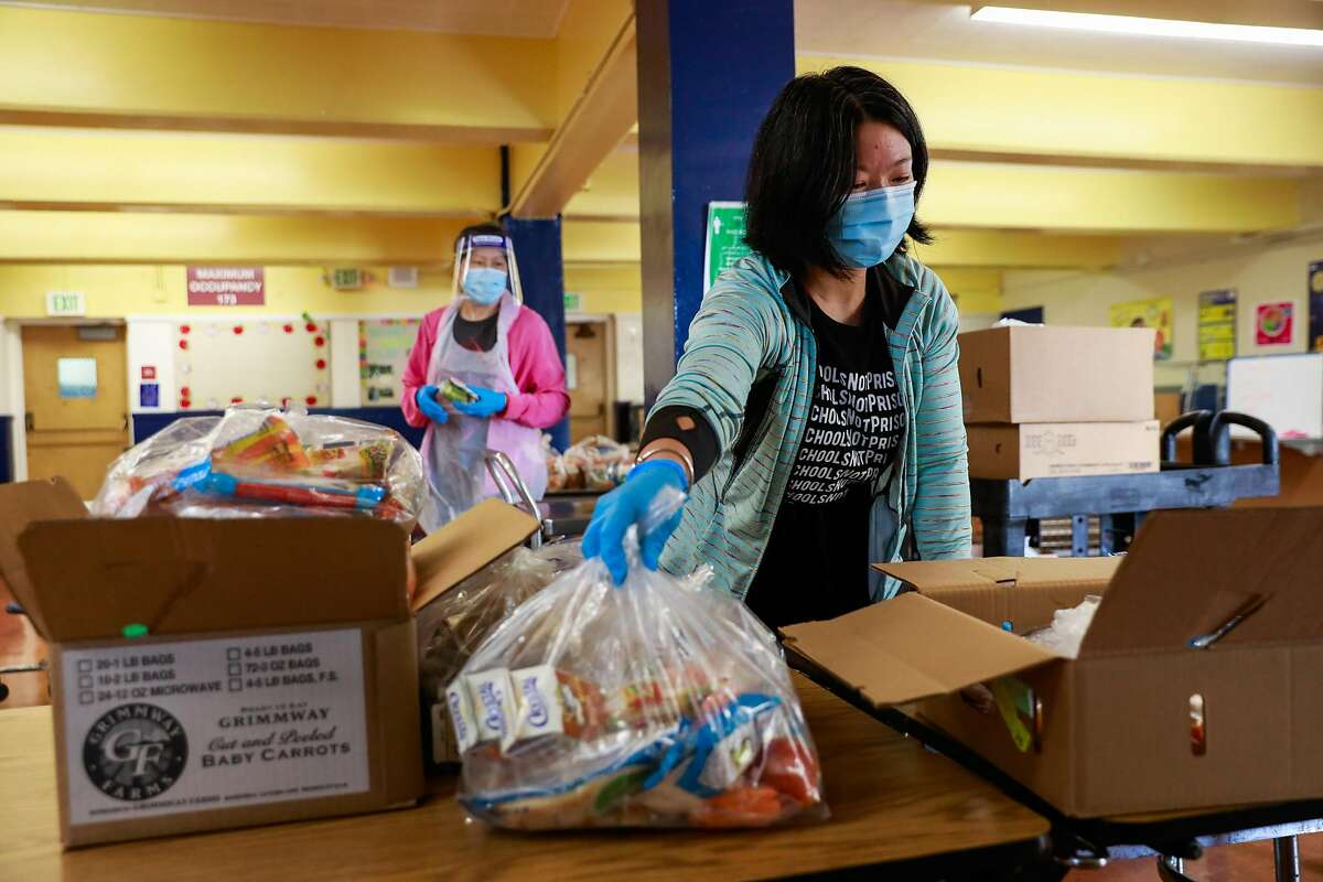 Wendy Li and Rachel Huang (right) prepare bagged lunch for students to take home at Sankofa Academy on the first day of school on Monday, Aug. 10, 2020 in Oakland, California.