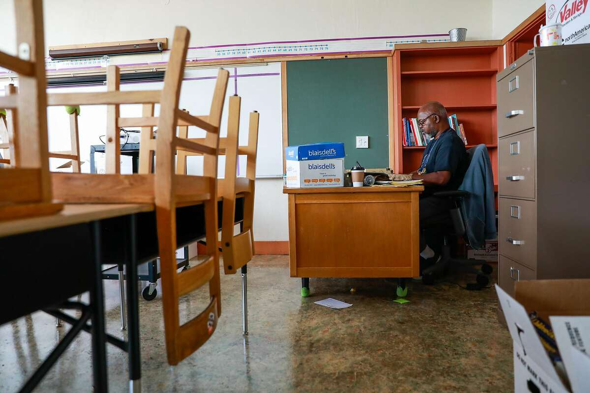 Fourth-grade teacher Mr. Peter Wilson teaches a zoom class from his empty classroom at Sankofa Academy on the first day of school on Monday, Aug. 10, 2020 in Oakland, California.