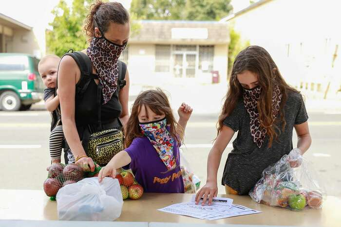 (L-r) Shel Jaeger, 1, mother Eleza Jaeger and her daughters Rhye Jaeger, 6 and Hazel Jaeger, pick up food and supplies at Sankofa Academy on the first day of school on Monday, Aug. 10, 2020 in Oakland, California.