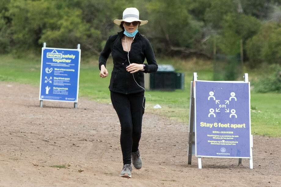 A woman jogging in Golden Gate Park runs past signs reminding people to social distance and wear mask in San Francisco, Calif. on July 28, 2020. Photo: Douglas Zimmerman / SFGATE