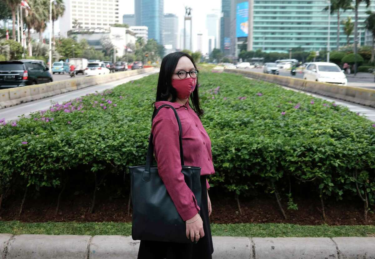 Clara Karina poses for a photo as she waits to cross a road after a job interview at the main business district in Jakarta, Indonesia, Thursday, Aug. 6, 2020. Around the world, young people armed with new degrees, diplomas and professional qualifications are struggling to enter the workforce as the pandemic pushes the global economy into recession. In Indonesia, Clara Karina, 25, graduated in January with an accounting degree from a well-known business and finance school in Jakarta. She wanted to work as a civil servant but applied for jobs at private firms as the government froze recruitment. It's been far from the easy process she imagined. (AP Photo/Dita Alangkara)