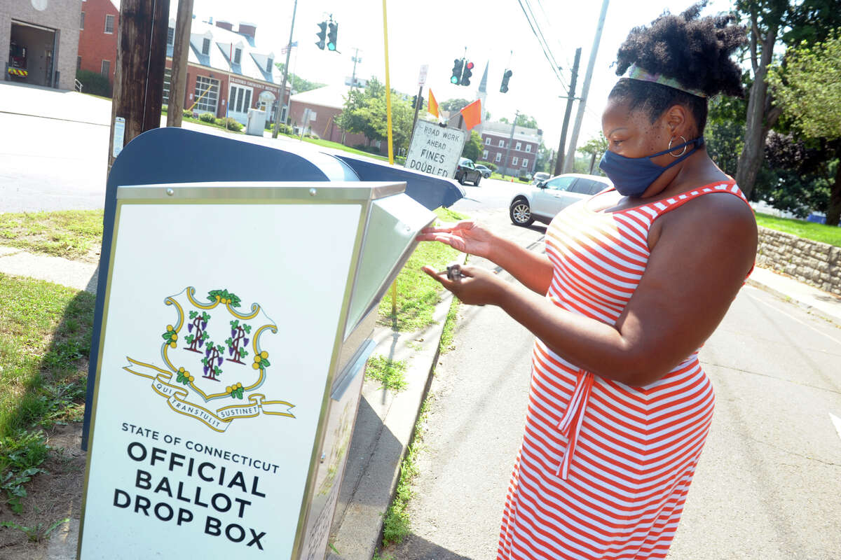 Aurelia William-Philpotts, of Stratford, drops her absentee ballot for Tuesday's primary elections into a state ballot drop box outside of Stratford Town Hall, in Stratford, Conn. Aug. 10, 2020.