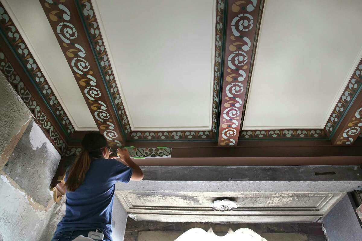 Gabby Duarte uses a stencil to recreate the original decorations along the edges of the ceiling in the building.